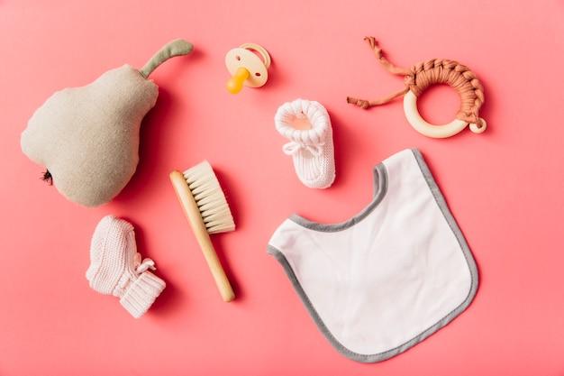 Vista superior do babador do bebê; chupeta; meia; escova; pêra recheada e brinquedo em fundo de pêssego Foto gratuita