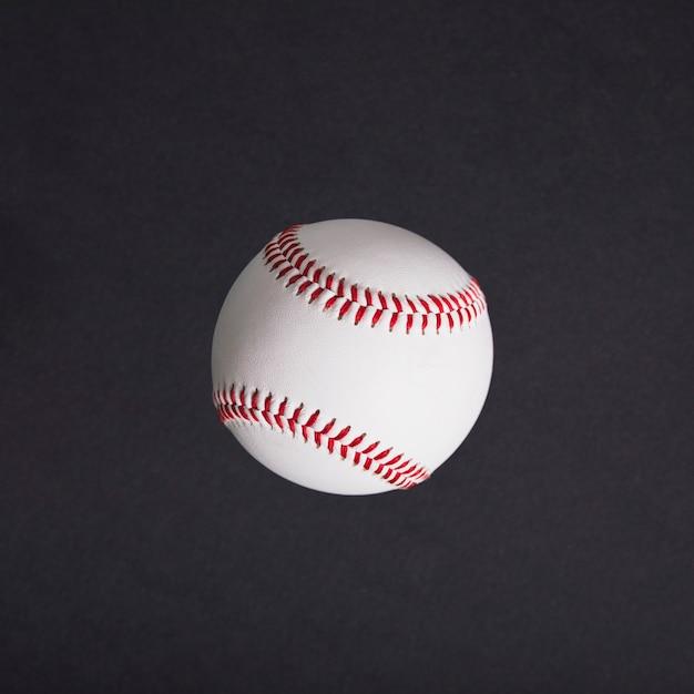 Vista superior do beisebol branco sobre fundo preto Foto gratuita