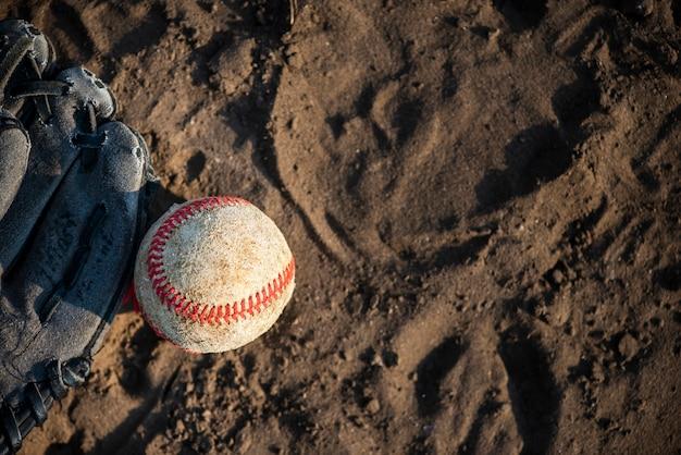 Vista superior do beisebol e luva na sujeira Foto gratuita
