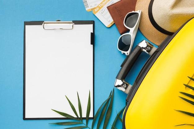 Vista superior do bloco de notas com bagagem e itens essenciais de viagem Foto gratuita