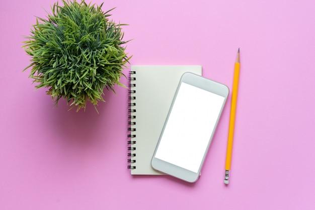 Vista superior do bloco de notas de smartphone maquete, lápis e planta em rosa Foto Premium