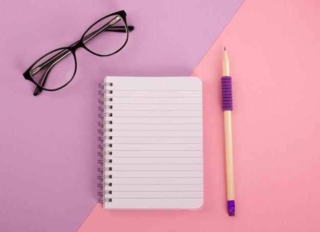 Vista superior do bloco de notas espiral, lápis de madeira e óculos em fundo rosa-lavanda. la plana Foto Premium