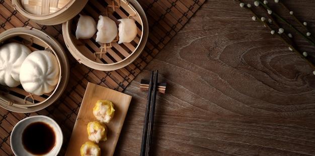 Vista superior do bolinho chinês cozido no vapor e pão de porco cozido no vapor em um vaporizador de bambu com pauzinho na mesa de madeira Foto Premium