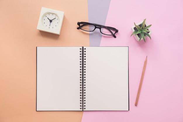 Vista superior do caderno com caneta, óculos, relógio Foto Premium