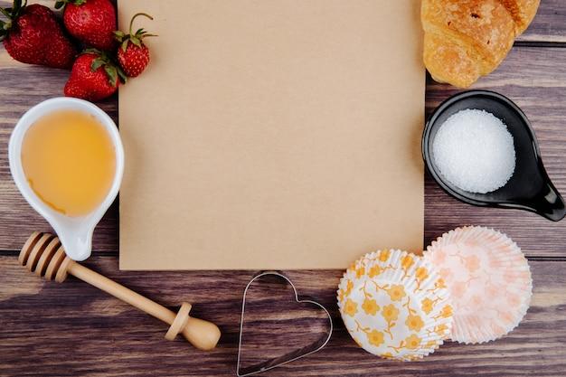 Vista superior do caderno e morangos frescos maduros com cortadores de croissant e biscoito de açúcar mel na madeira Foto gratuita