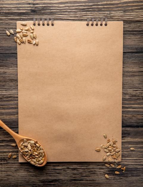 Vista superior do caderno e uma colher de pau com sementes de girassol no rústico Foto gratuita
