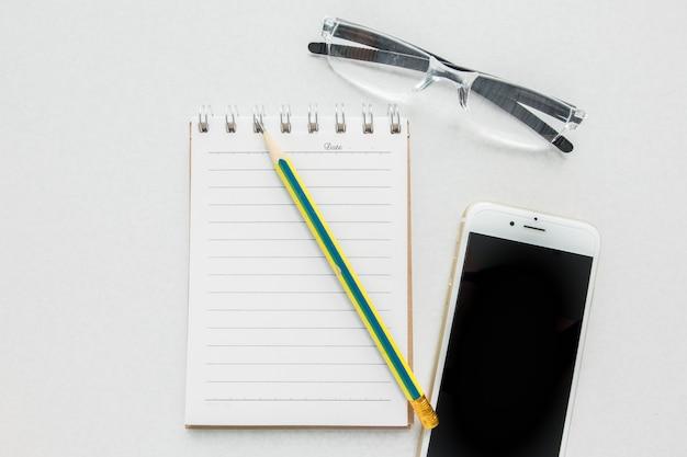Vista superior do caderno em branco com lápis, óculos de leitura e telefone móvel esperto na mesa branca. Foto Premium