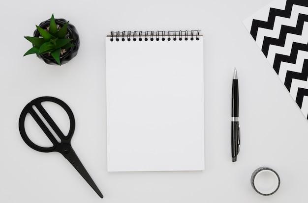 Vista superior do caderno em branco com tesoura e planta Foto gratuita