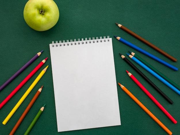 Vista superior do caderno em branco, lápis de cor e maçã verde Foto Premium