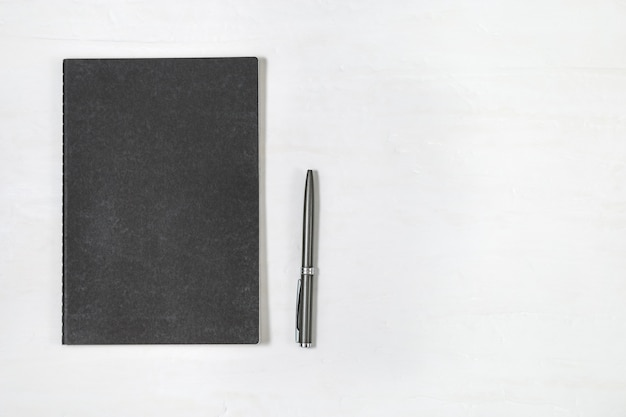 Vista superior do caderno fechado da tampa preta com a pena brilhante no fundo branco da mesa. mock up copybook. mínima mesa de escritório com artigos de papelaria. Foto Premium