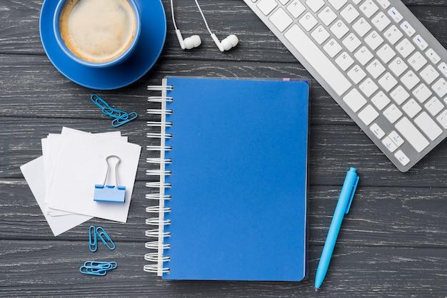 Vista superior do caderno na mesa de madeira com notas auto-adesivas e xícara de café Foto gratuita