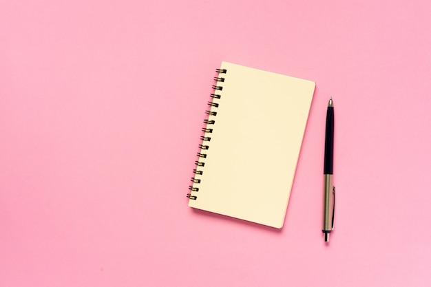 Vista superior do caderno vazio com caneta no conceito de fundo de cor rosa Foto Premium