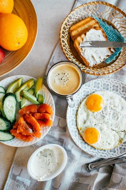 Vista superior do café da manhã com ovo, salmão, abacate, pepino, xícara de café e pão grelhado com creme de queijo. comida caseira. café da manhã da noruega. Foto Premium