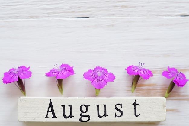Vista superior do calendário de madeira com sinal de agosto e flores cor de rosa. Foto Premium