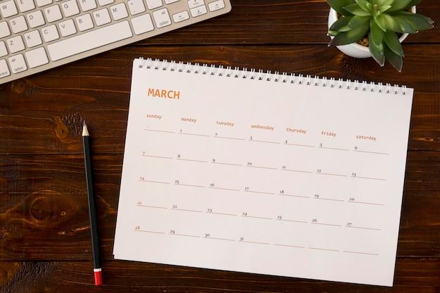 Vista superior do calendário de mesa na mesa de madeira Foto gratuita
