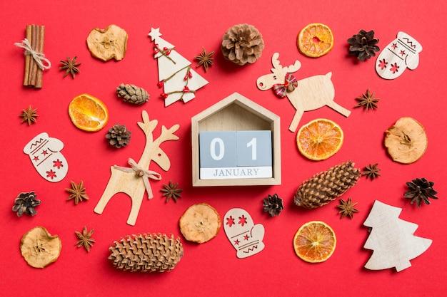 Vista superior do calendário decorado com brinquedos festivos e renas de símbolos de natal e árvores de ano novo. o primeiro de janeiro. conceito de férias Foto Premium