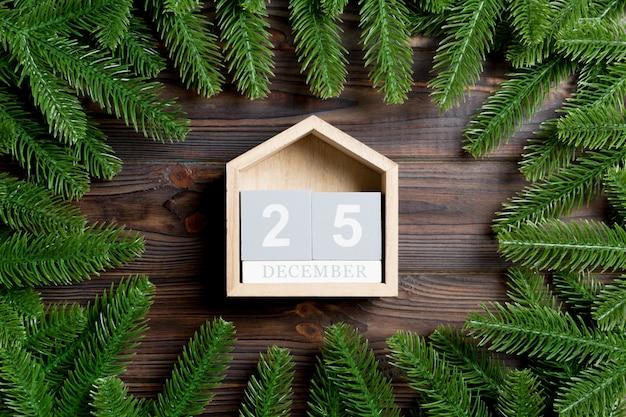 Vista superior do calendário decorado com uma moldura feita de abeto na mesa de madeira. o vigésimo quinto de dezembro. conceito de tempo de natal Foto Premium