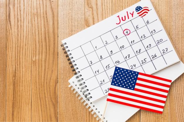 Vista superior do calendário do mês de julho com bandeiras americanas e espaço de cópia Foto gratuita