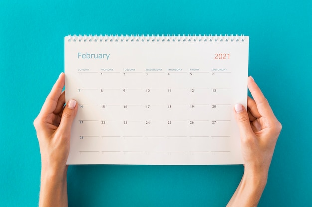 Vista superior do calendário e mãos do planejador Foto gratuita