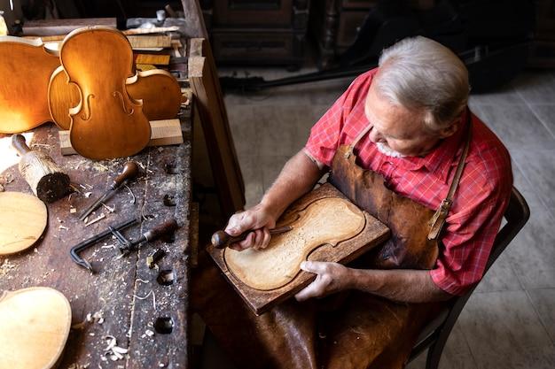 Vista superior do carpinteiro sênior trabalhando em sua oficina antiquada Foto gratuita