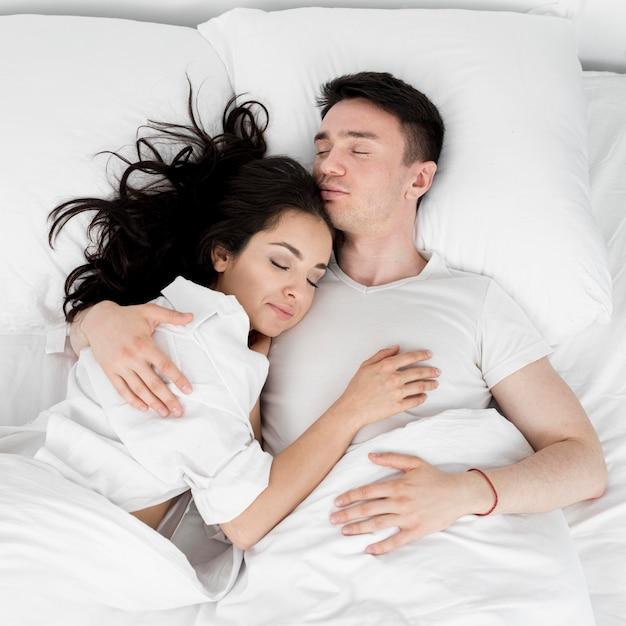 Vista superior do casal dormindo juntos na cama Foto gratuita