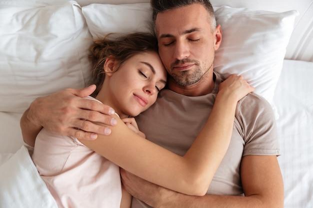 Vista superior do casal muito amoroso dormindo juntos na cama em casa Foto gratuita