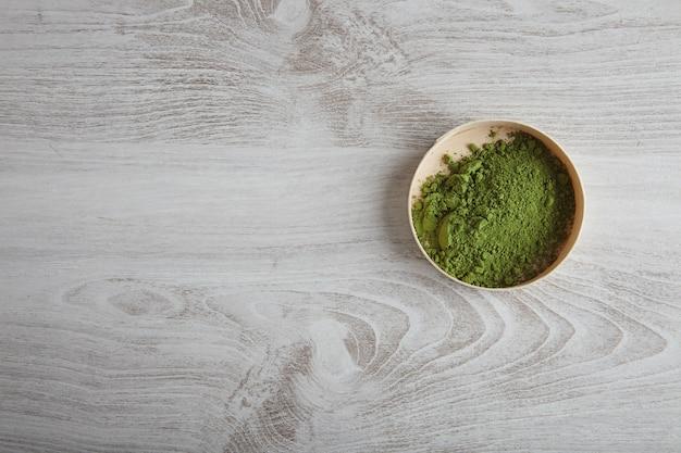 Vista superior do chá matcha orgânico premium em pó em uma caixa de madeira isolada na mesa branca simples Foto gratuita