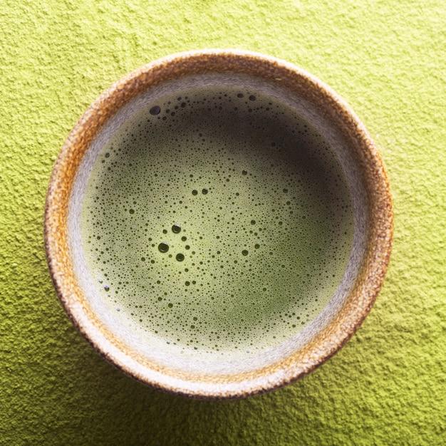 Vista superior do chá verde matcha em uma tigela sobre uma superfície em pó Foto Premium