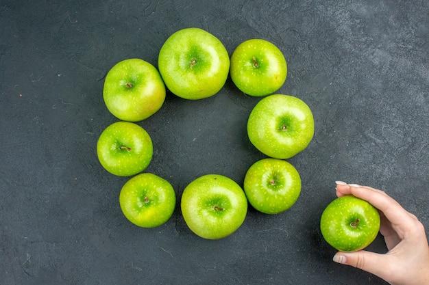 Vista superior do círculo linha maçã verde maçã na mão da mulher na mesa escura Foto gratuita