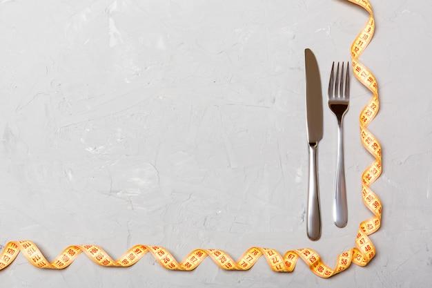 Vista superior do conceito de obesidade com garfo, faca e fita métrica enrolada em fundo de cimento com espaço para suas idéias criativas Foto Premium