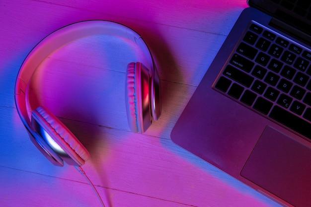 Vista superior do conjunto de dispositivos em luz de néon roxa e fundo rosa. teclado do laptop, fones de ouvido e smartphone com tela preta. copyspace para sua publicidade. tecnologia, moderna, gadgets. Foto gratuita