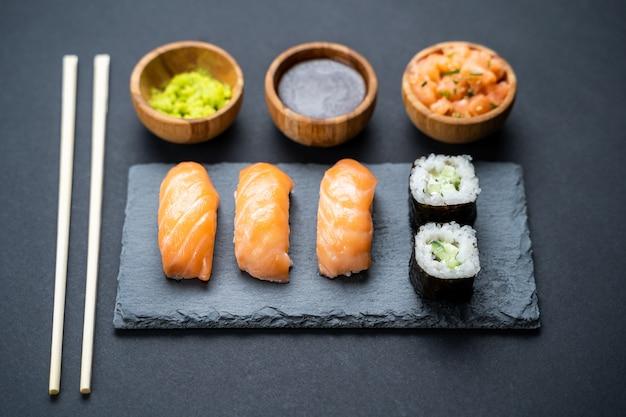 Vista superior do conjunto de rolos de sushi, maki, uramaki, nigiri e sashimi servido na ardósia de pedra. Foto Premium