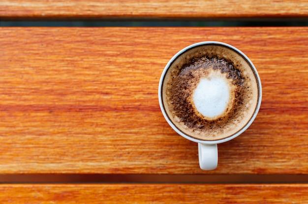 Vista superior do copo de café no fundo da mesa de madeira Foto gratuita