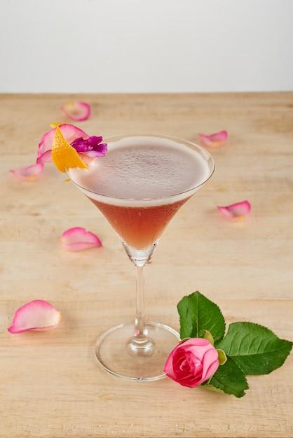 Vista superior do copo de coquetel decorado em pé sobre uma mesa vazia com rosa fresca na parte inferior Foto gratuita