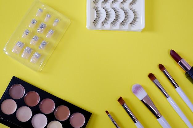 Vista superior do cosmético das mulheresâ € ™ s no fundo amarelo. Foto Premium