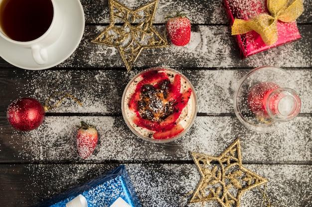 Vista superior do deserto de morango servido com chá com decorações de natal Foto gratuita