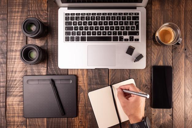 Vista superior do desktop de madeira com laptop, mesa, café, notebook, celular, cartões de memória. Foto Premium