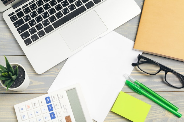 Vista superior do desktop de madeira com óculos e artigos de papelaria close-up. brincar Foto Premium
