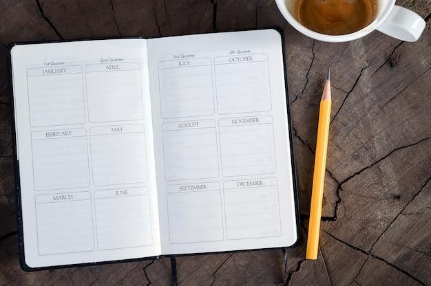 Vista superior do diário aberto da página com lápis e a xícara de café amarelos no fundo de madeira. Foto Premium