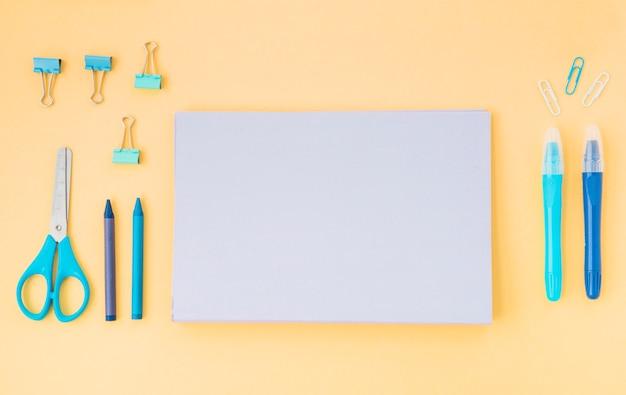 Vista superior do diário; giz de cera; tesoura e clipes de papel dispostos em papel colorido Foto gratuita
