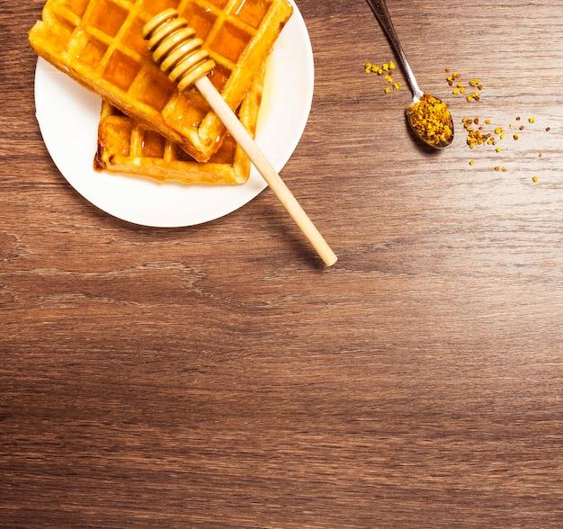 Vista superior do doce waffle belga com mel e pólen de abelha Foto gratuita