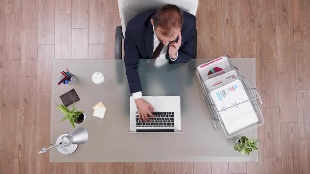 Vista superior do empresário de terno discutindo lucro on-line com o gerente no telefone Foto gratuita