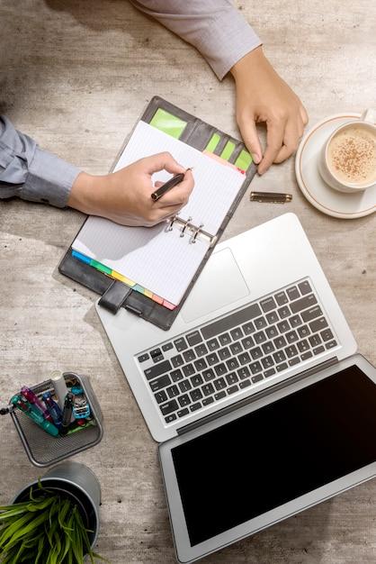 Vista superior do empresário escrevendo no bloco de notas com laptop, café, planta em vaso e acessórios de negócios Foto Premium