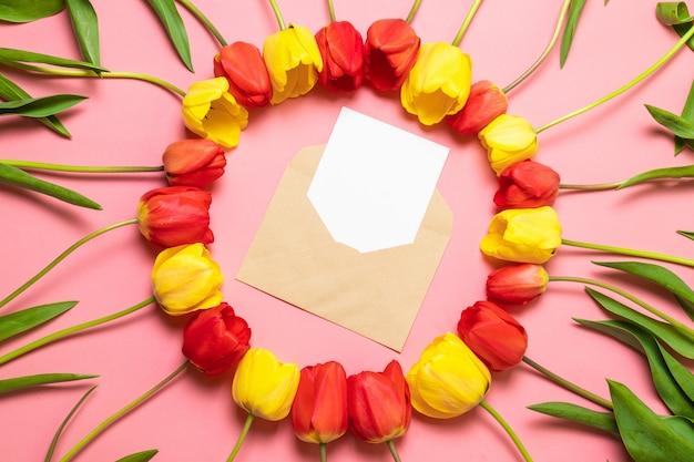 Vista superior do envelope e quadro de tulipas vermelhas em fundo rosa. Foto Premium