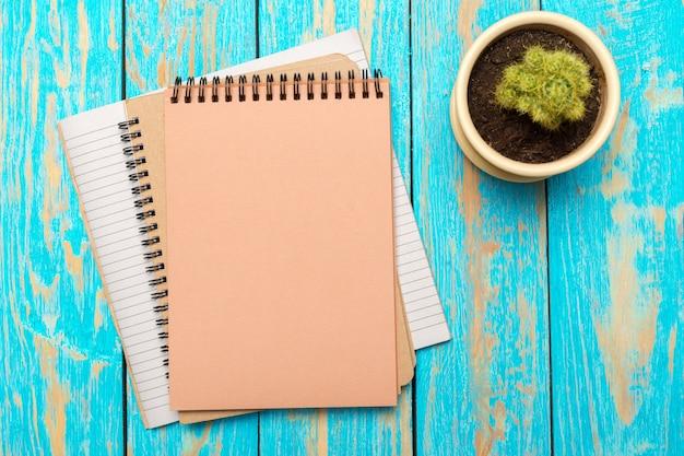 Vista superior do espaço de trabalho com o caderno em branco e caneta na mesa de madeira Foto Premium