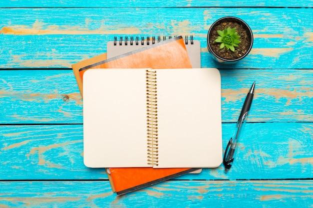 Vista superior do espaço de trabalho com o caderno em branco e caneta no fundo da mesa de madeira Foto Premium