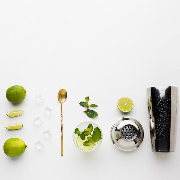 Vista superior do essencial de coquetel com agitador e limão Foto gratuita