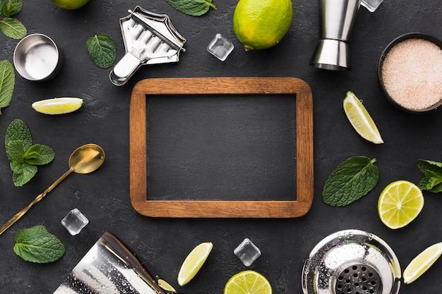 Vista superior do essencial de coquetel com lousa e limão Foto gratuita