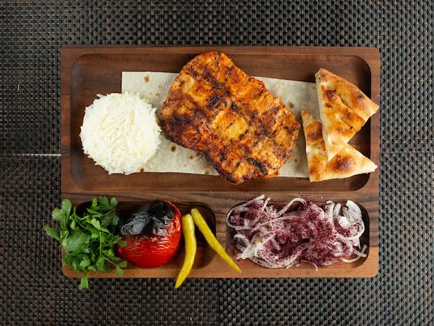 Vista superior do filé de frango grelhado servido com cebola e legumes de pão de arroz Foto gratuita