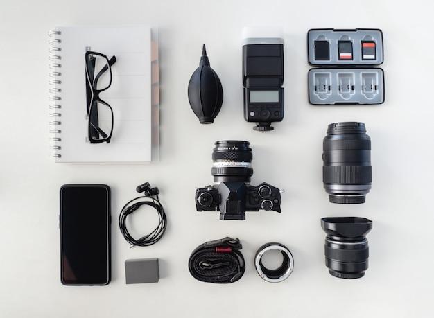 Vista superior do fotógrafo de espaço de trabalho com câmera digital, flash, kit de limpeza Foto Premium